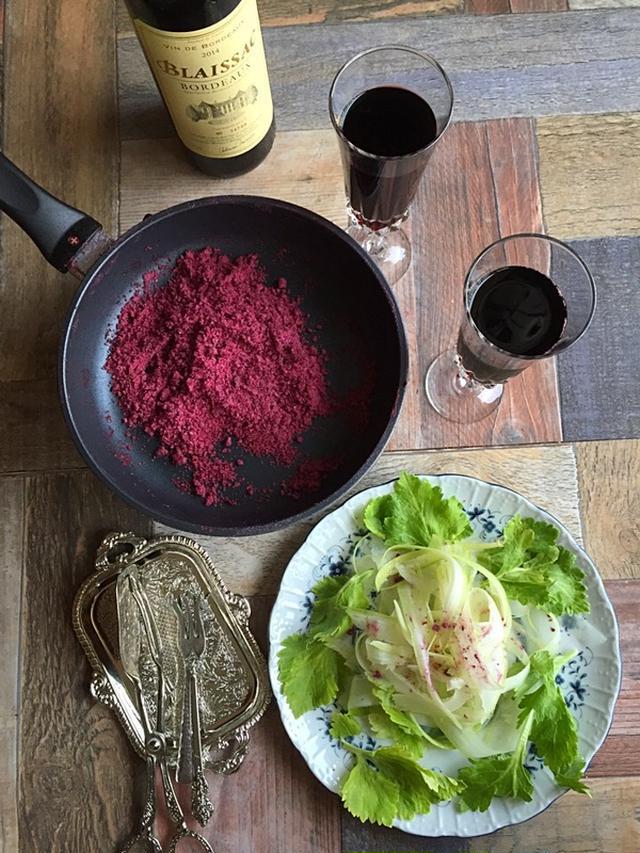 奥からワインの瓶、赤ワインが入ったグラスが2つ。フライパンにワインハーブ塩。手前に白い皿にサラダ。隣に銀食器。