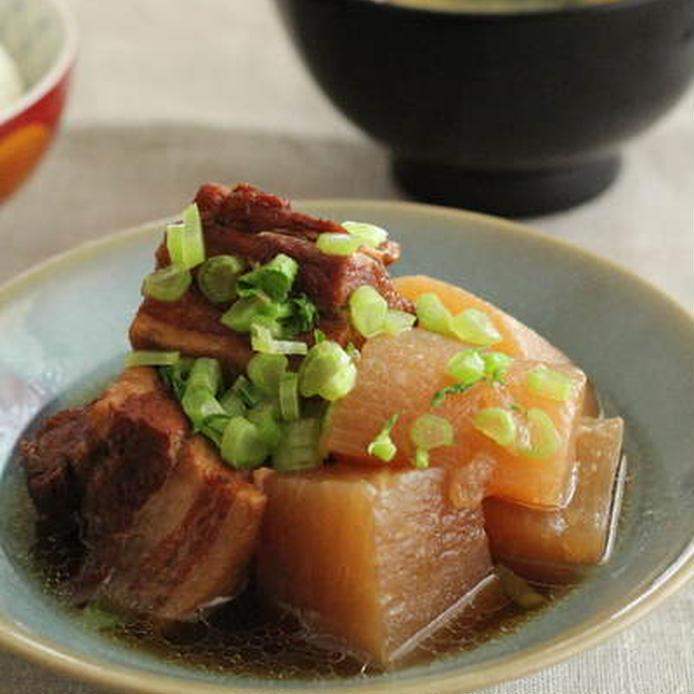 薄い青灰の皿に盛られた、豚バラ肉と大根の煮物