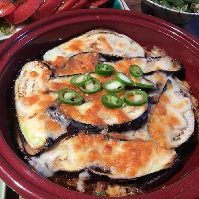 えんじ色の丸いお皿に盛られた茄子と豚こまのチーズ焼き
