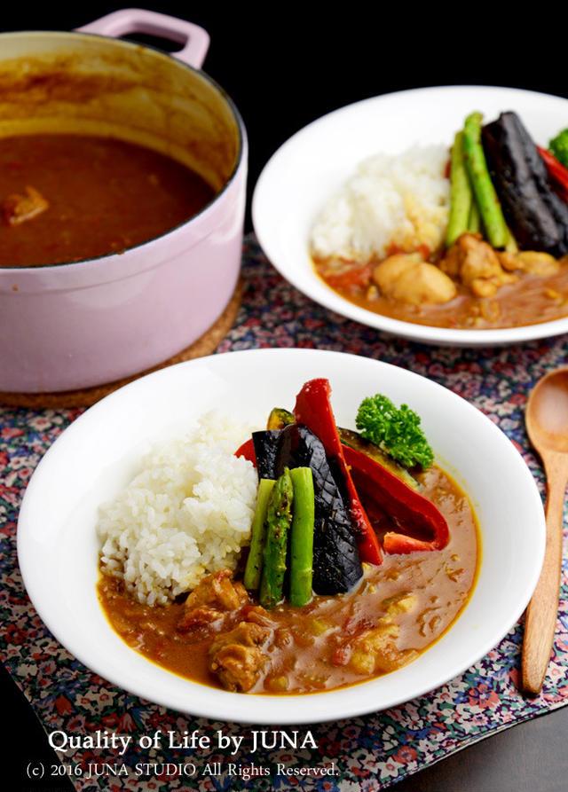 カレーの入った鍋と、丸い白いさらに盛られたアスパラ、ナス、パプリカがトッピングされたの無水カレー