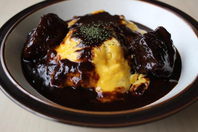 半熟卵のオムライスにかかった濃い色のビーフシチュー