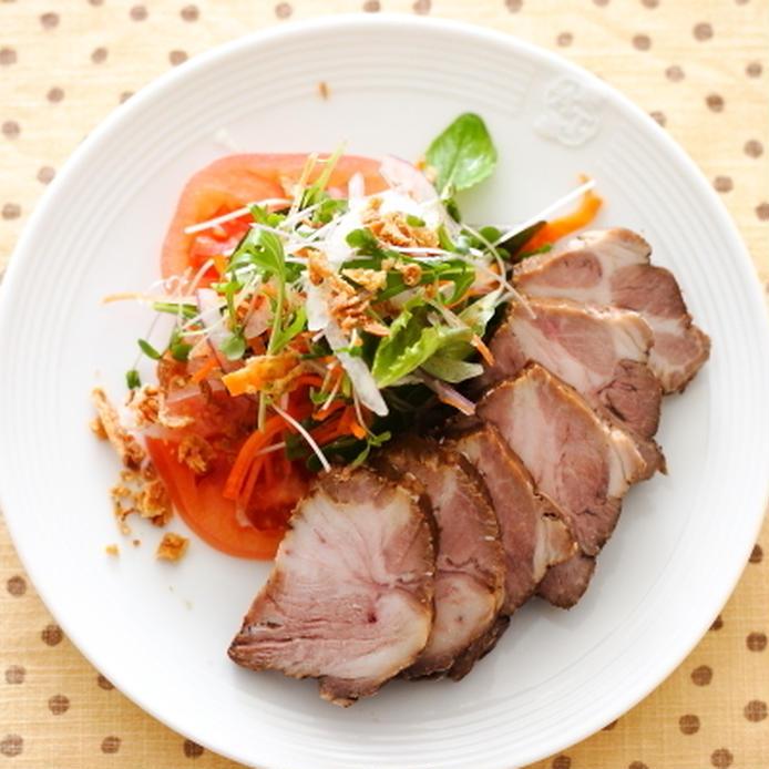 白い丸皿に盛られた紅茶豚のスライスとサラダ