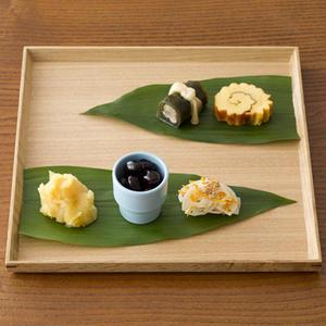 白木のトレイに葉らんを互い違いに2枚敷き、おせち料理を少しずつ感覚をあけて盛ります。来客のときなど、...