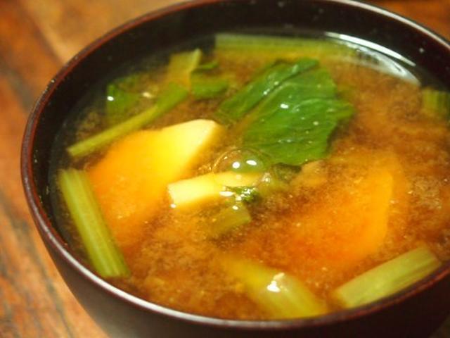黒い茶碗に盛られたじゃがいもと小松菜の味噌汁