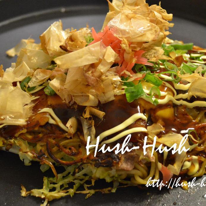 ネギや紅生姜が盛られたモダン焼きが黒の皿に盛られている