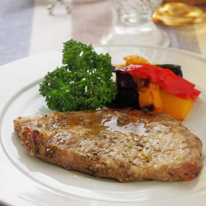 白いお皿に品良く盛られたポークステーキと付け合わせ野菜