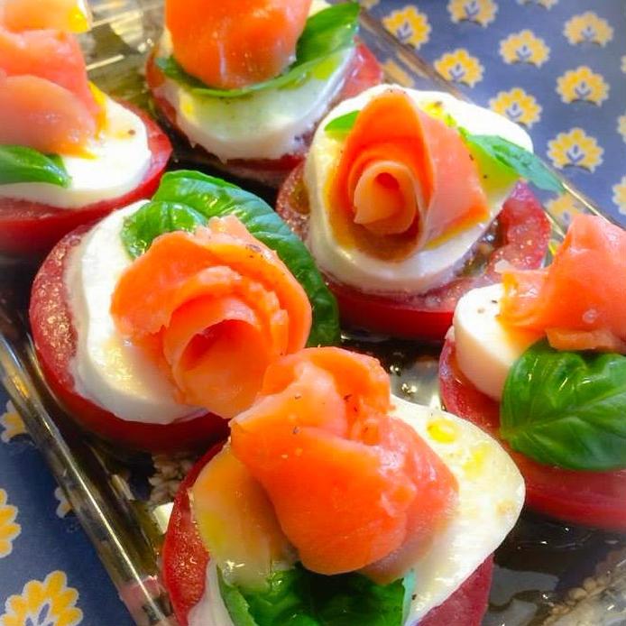 トマトの上にクリームチーズとバラの形に切られたサーモンとバジルがのったカプレーゼ
