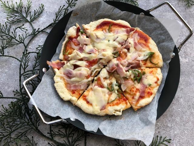 黒いフライパンの上に盛られたピザ、飾りの植物