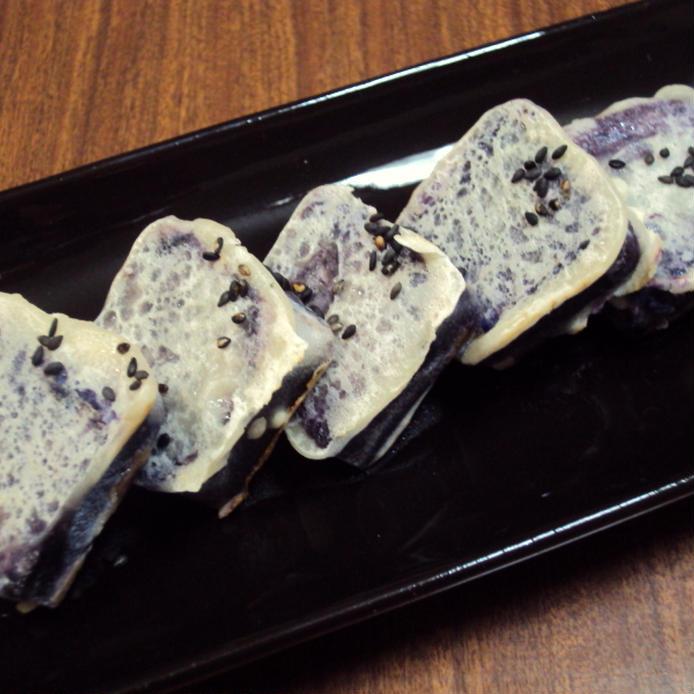 黒い細長い皿に盛られた紫芋のきんつば