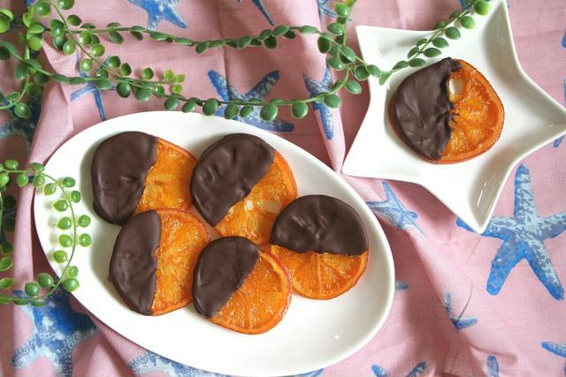 丸の皿と星型の皿にチョコでコーティングしたオレンジが置かれている