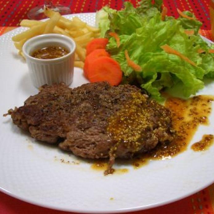白い丸皿に盛られた、牛薄切り肉のステーキと野菜、ポテト