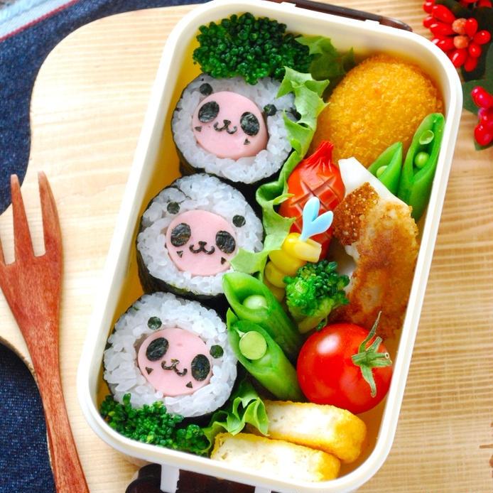 パンダの顔がデコレーションされた魚肉ソーセージ入りの海苔巻きと、数種類のおかずが、白いお弁当箱の中に詰められている。