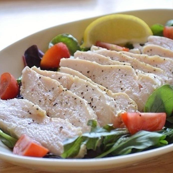 楕円形の白いお皿に盛られたガーリックコンソメ風味のサラダチキンと付け合わせの野菜