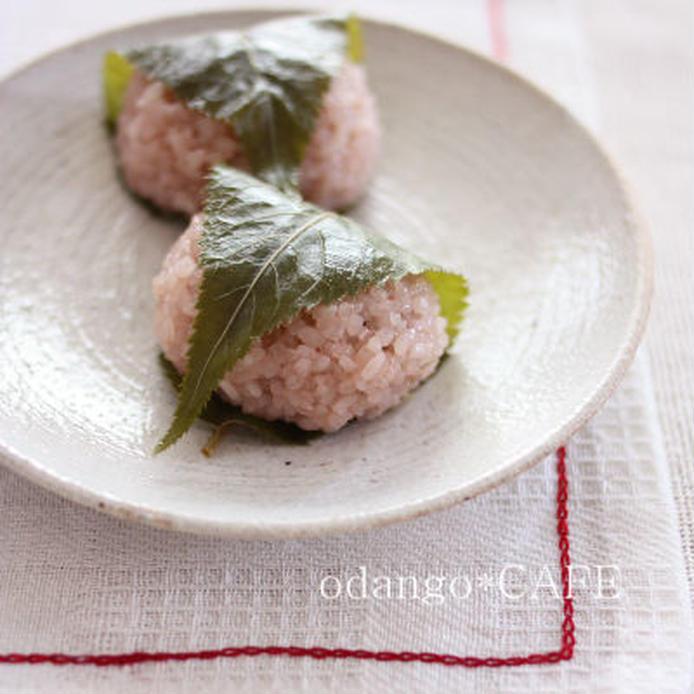 白っぽい陶器の丸皿に盛られた2つの桜餅