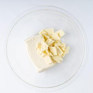 2、耐熱のボウルにクリームチーズとホワイトチョコを手で砕いて入れ、ラップをせずに電子レンジ(600W...