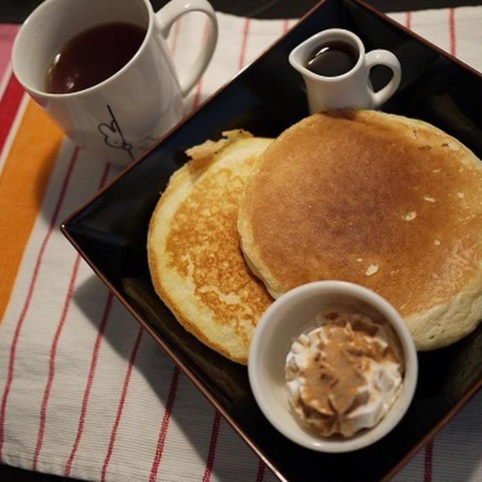 牛乳や卵を使わずに作られたパンケーキが黒いお皿に盛られ、メープルシロップと生クリームが添えられている