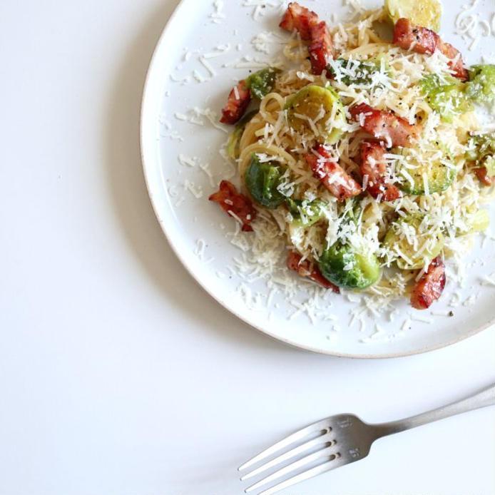 白い大皿に盛られた芽キャベツとベーコンのパスタ