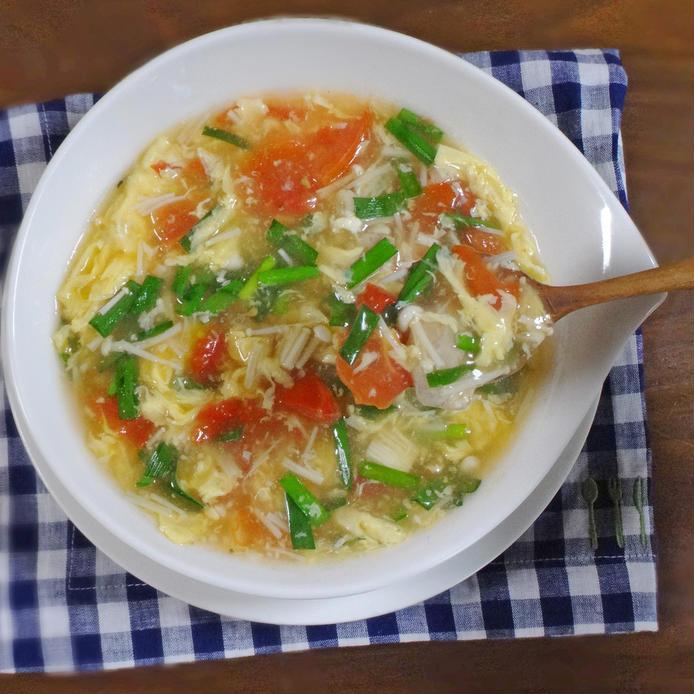 白いスープ皿に盛られた、鶏肉とトマト・ニラ・エノキの卵とじスープ
