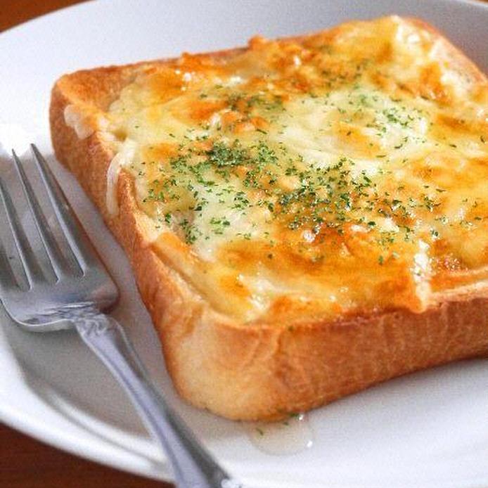 白の皿に盛られたトーストにチーズとはちみつがたっぷりかかっている