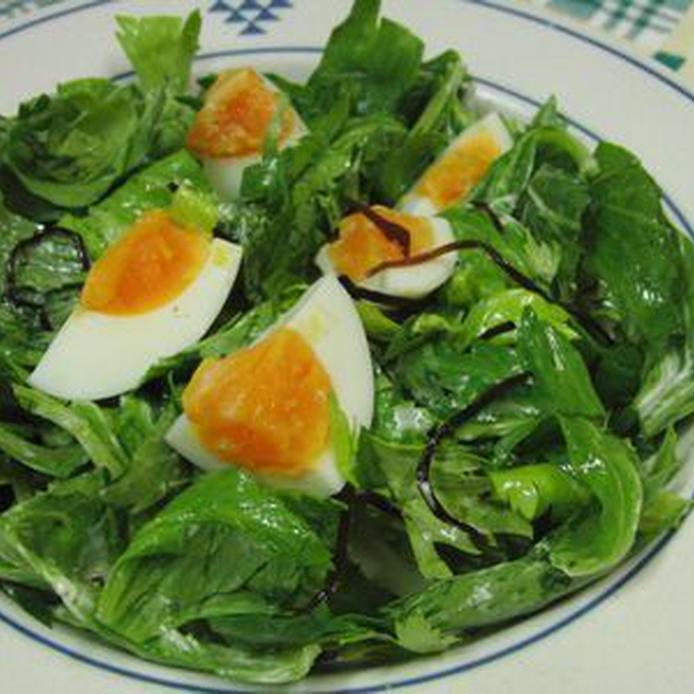 白い皿に盛られた、セロリの葉のグリーン卵サラダ