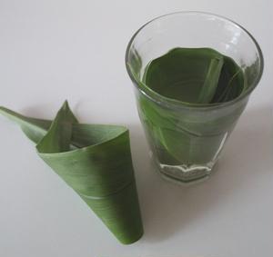 2.クルクマの葉を丸めて、グラスに沈めます。(3枚中1枚はお料理の皿の飾りに使用)