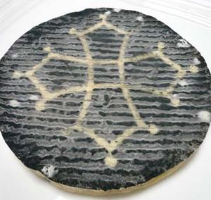 黒が印象的なチーズの表面に浮かび上がるのは、中世の雰囲気を漂わせるオクシタンの十字架を灰でかたどった...