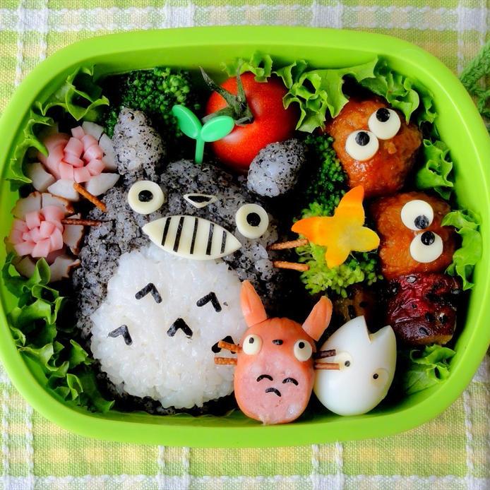 緑色のお弁当箱の中に、ゆかりご飯の大トトロと、ウインナーの中トトロと、うずらの卵の小トトロが詰められている。