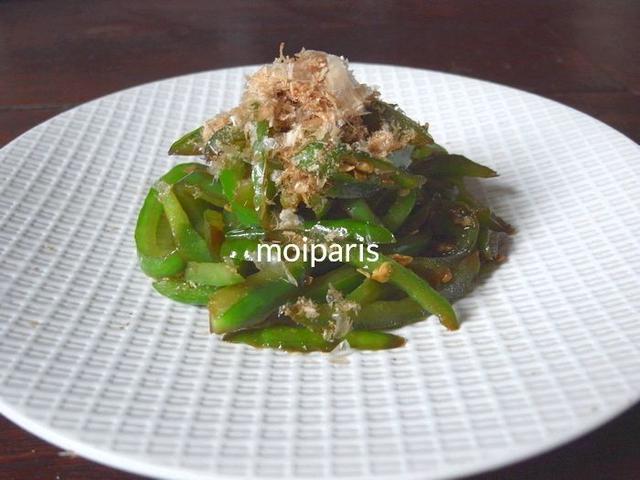 白の皿の中心に盛られたピーマンと青唐辛子の炒め物