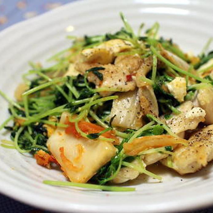 丸いお皿に盛られた豆腐と豆苗と鶏むね肉のキムチ炒め