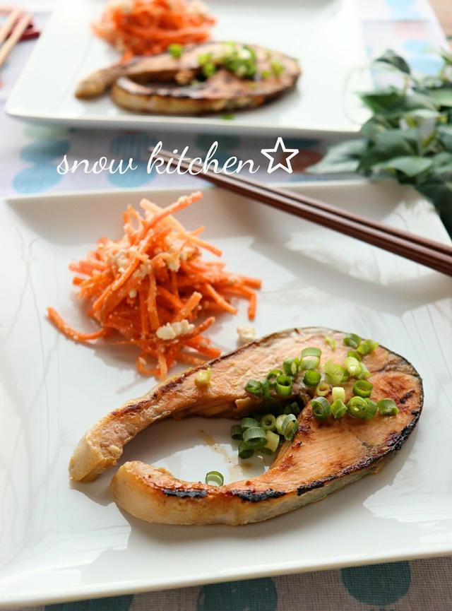 白いプレートに乗った輪切りの焼き鮭と人参の副菜