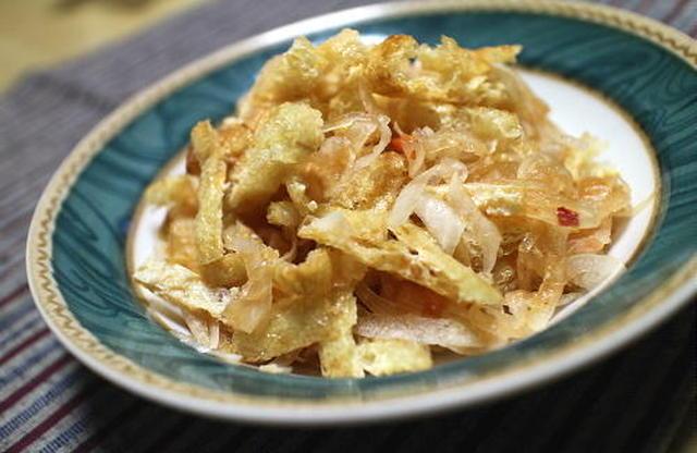 青の柄の皿に盛られた玉ねぎと油揚げのサラダ
