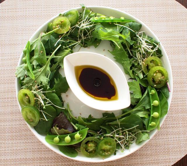 ドレッシングを中心にブロッコリースプラウトやその他の葉物の野菜、緑の豆が円状に並べられたサラダ