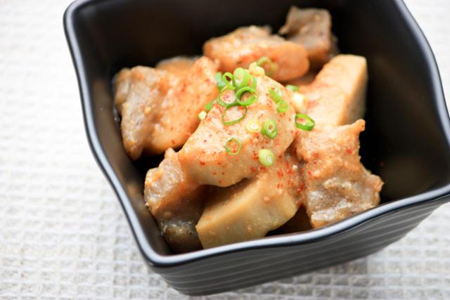 一味唐辛子とねぎがトッピングされたサトイモの煮もの