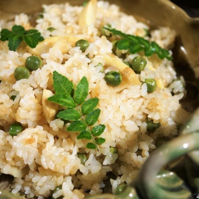 陶器の器に盛られたグリーンピースとたけのこのバター醤油炊き込みご飯と飾りの葉山椒