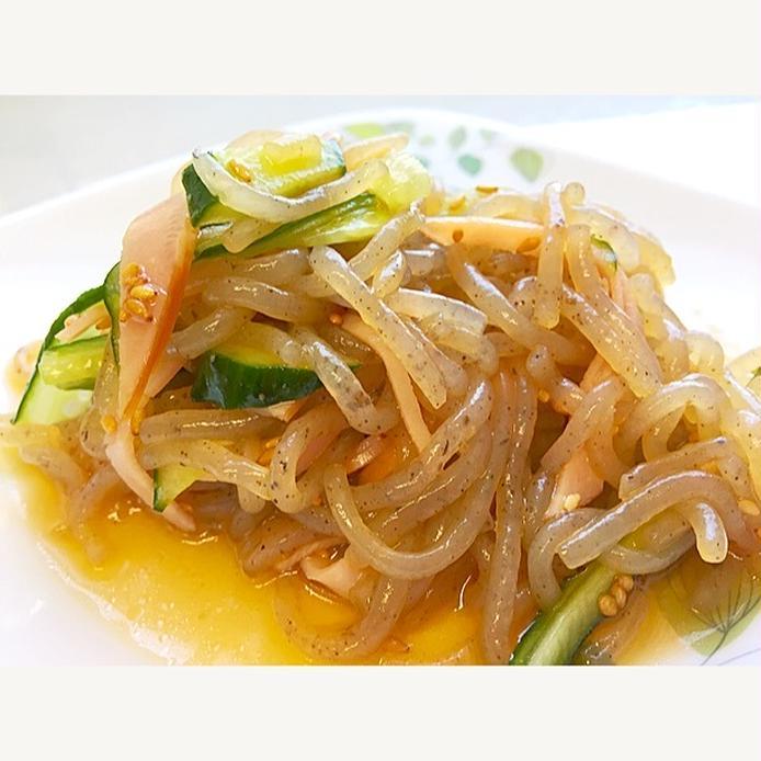 植物の模様が入っている皿に盛られた、糸こんにゃくときゅうりとハムのサラダ
