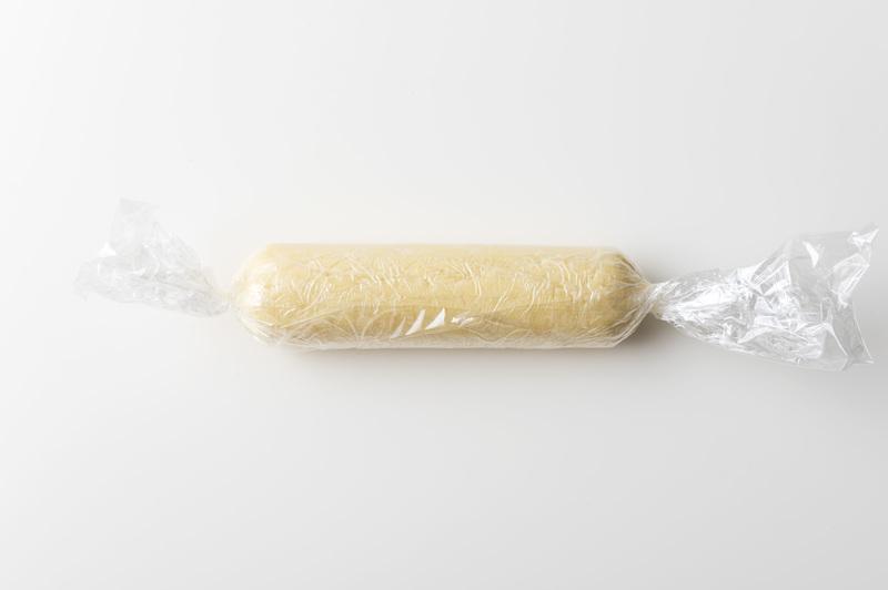 4、ラップで包んで棒状に成形し、冷蔵庫で13分ほど冷やし、切りやすいかたさにする。
