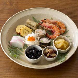 大きめのお皿にうらじろなどを敷いて、おせち料理を盛ります。豆のように小さいものや、ほかの料理と味がま...