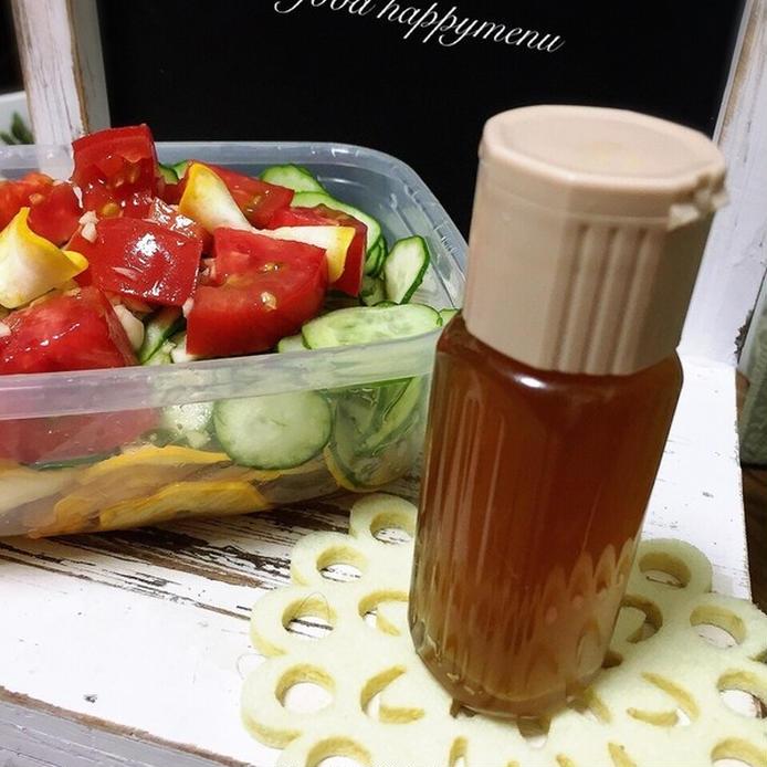ボトルに入ったドレッシングと保存容器に入ったビタミンカラーのサラダ