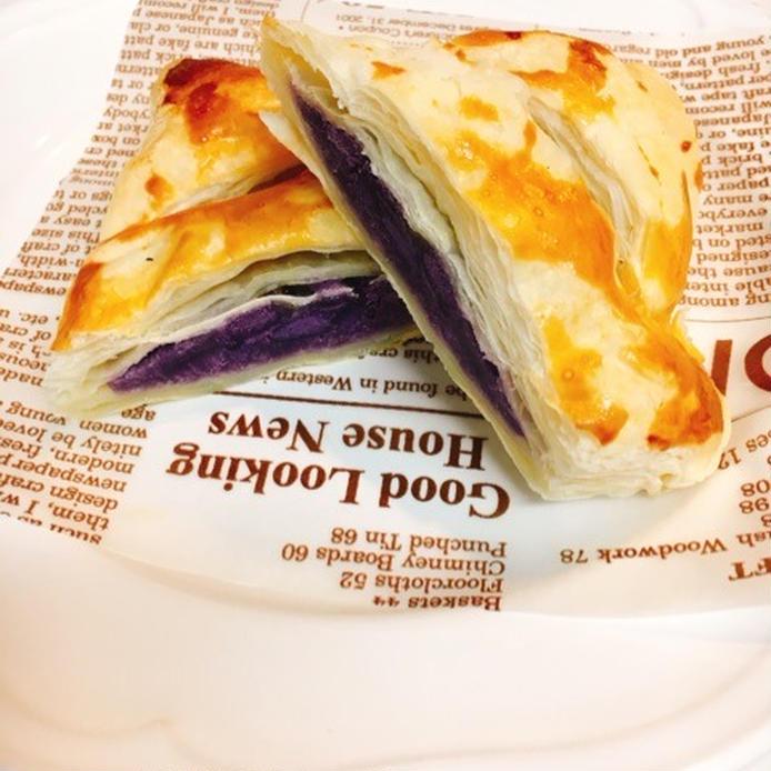 英字のワックスシートに置かれた斜めに半分に切られた紫芋のスイートポテトパイ