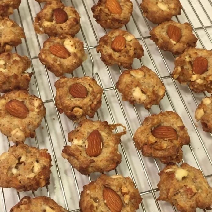 網の上に並べられた、レモンピール入りのアーモンドドロップクッキー