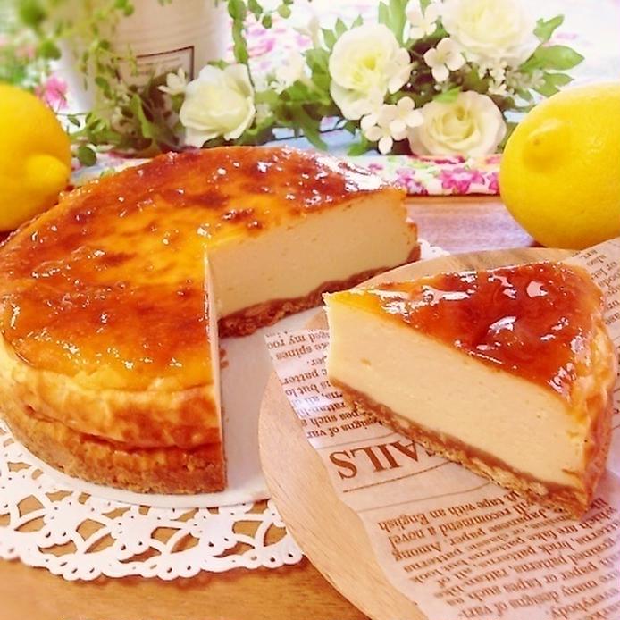 レースペーパーと英字ペーパーの上に盛り付けたホールチーズケーキ、飾りのレモン、白い薔薇