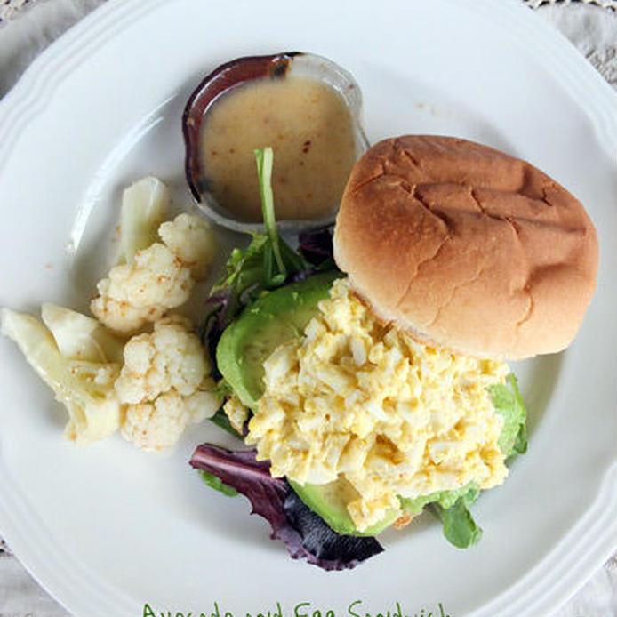 白いプレートに盛り付けたアボカドと卵のサンドイッチ