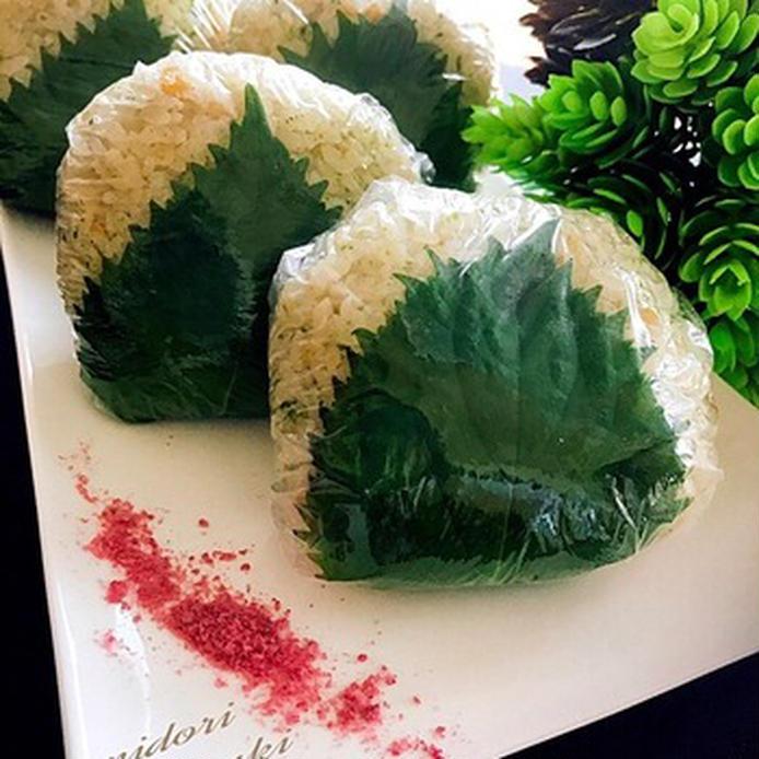 白いお皿に置かれた大葉で挟んだ緑の天かすおにぎり
