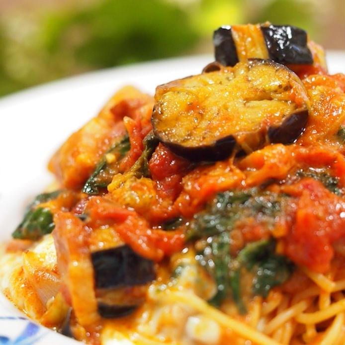 白いパスタ皿に盛られたなすとモッツァレラのトマトスパゲッティ